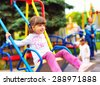 cute happy girl, kid having fun on swings at playground - stock photo
