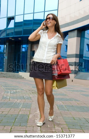Cute happy girl on a street after successful shopping speaking by mobile phone. Mall on the background
