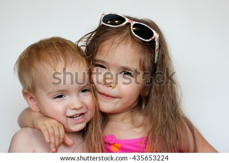 Cute happy girl wearing swimming suit and sun glasses with her small brother over white background, summer vacation concept - stock photo