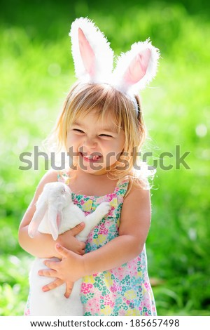 Cute happy girl with a real easter bunny wearing ears at spring green grass - stock photo