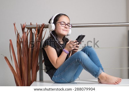 Cute happy girl with glasses listening to music on headphones - stock photo