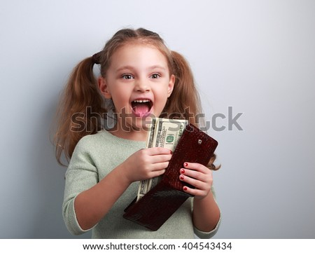 Cute happy kid girl holding wallet with much dollars with open mouth. Portrait - stock photo
