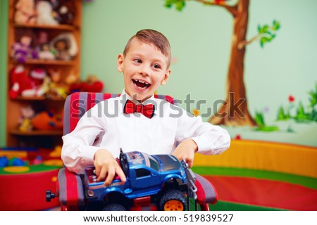 cute happy kid on wheelchair with present in kindergarten for kids with special needs