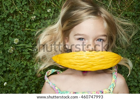 Cute happy little blond girl with melon lying on the grass in summertime