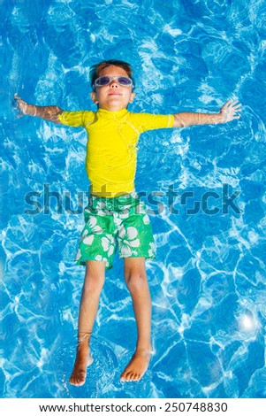 Cute happy little boy in goggles swimming and snorking in the swimming pool