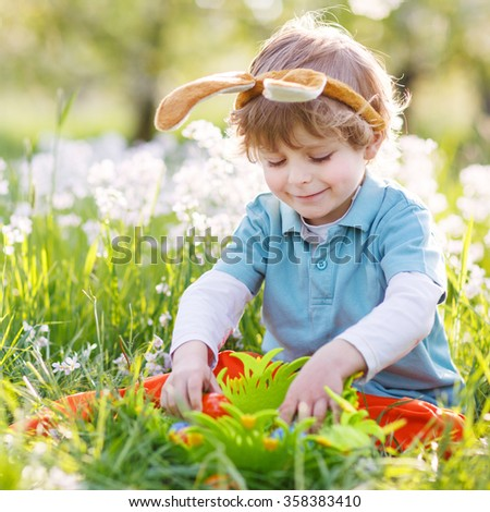 Cute happy little boy wearing Easter bunny ears and playing with colorful eggs in box, lauging and having fun outdoors.