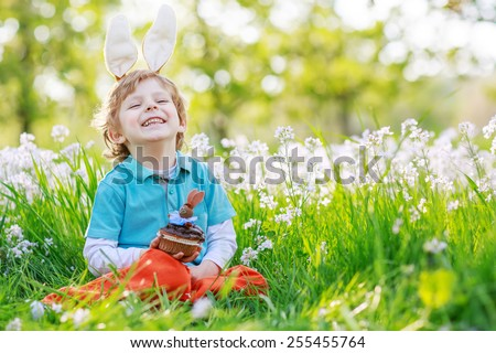 Cute happy little boy wearing Easter bunny ears at spring green grass and blooming apple garden, eating chocolate muffing with bunny and having fun outdoors. - stock photo