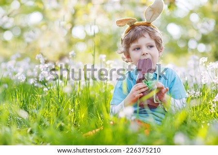 Cute happy little child wearing Easter bunny ears at spring green grass and blooming apple garden, eating chocolate bunny and having fun outdoors.