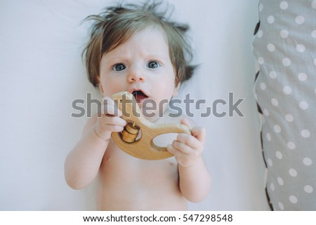 Cute  happy little four month old baby girl lying on the white sheet with wooden toys.