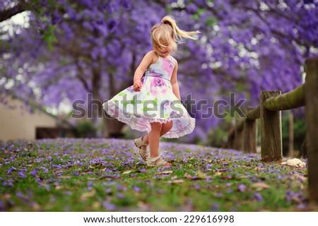 Cute happy little girl in blooming park. Beautiful Jacaranda - stock photo