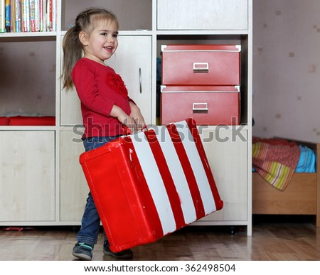Cute happy little girl lifting red and white fascinated vintage suitcase and carry it, indoor portrait - stock photo