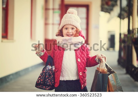 Cute happy little girl on shopping. Portrait of a kid with shopping bags.