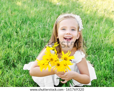 Cute happy little girl on the meadow with flower in summer day