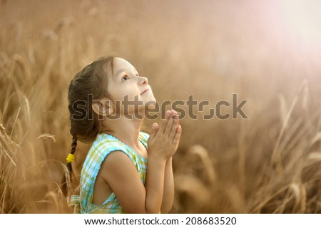 Cute happy little girl prays in wheat field - stock photo