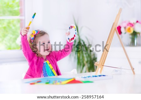 Cute happy little girl, preschooler, painting with water color on canvas standing on easel in a sunny white room at home or elementary school, creative young artist at work. Kids paint. Children draw. - stock photo