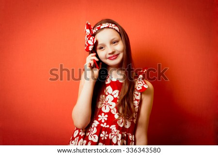 Cute happy little girl talking on the phone with your favorite - stock photo