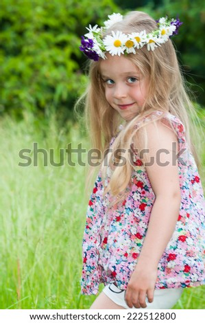 Cute happy little girl with a flower wreath at Midsummer - stock photo