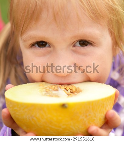 cute happy little girl with melon - stock photo