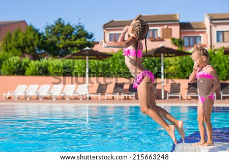 Cute happy little girls having fun in the swimming pool - stock photo