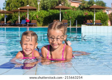 Cute happy little girls having fun in the swimming pool