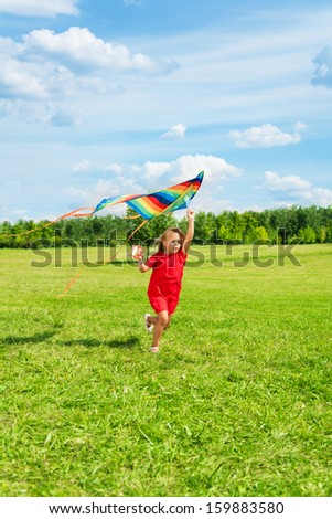 Cute happy little 6 years old girl with blond hair running holding kite in the field on summer sunny day
