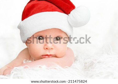cute happy newborn baby in christmas hat - stock photo