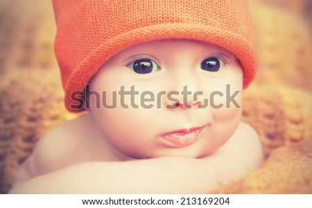 cute happy newborn baby in knitted orange hat cap - stock photo