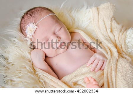 Cute happy newborn girl with a headband is sleeping in a fur.  - stock photo