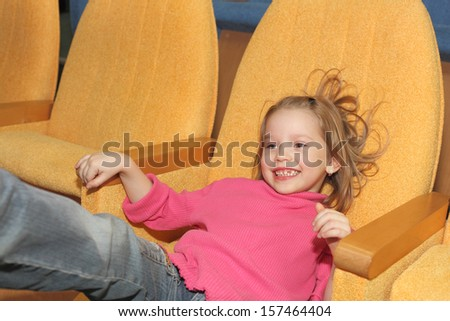 cute happy pretty smiling little girl sitting in the cinema hall - stock photo