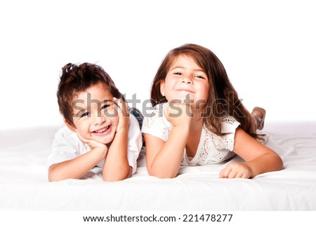 Cute happy smiling brother sister sibling family laying next to eachother, on white.