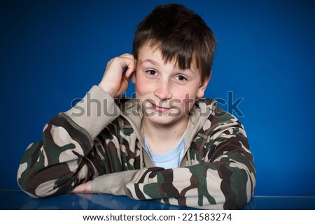 cute happy teenager boy on a blue background - stock photo