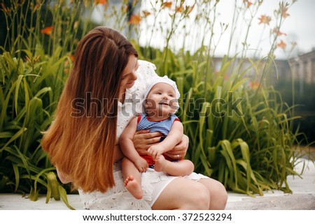 Cute Happy Toddler Sitting on Loving Mother`s Knees and Smiling. Family Fun. Selective Focus. - stock photo