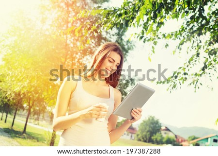 Cute happy young Caucasian brunette teenage woman with tablet computer and takeaway coffee in park on sunny summer day.  - stock photo