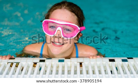 Cute happy young girl child relaxing on the side of a swimming pool wearing pink goggles mask - stock photo