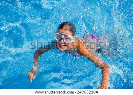 Cute happy young girl in goggles swimming and snorking in the swimming pool