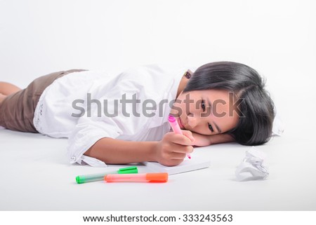 cute happy young girl writing something in her notebook