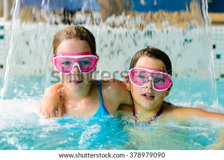 Cute happy young girls children playing in swimming pool under  a cascade of water - wearing pink goggles mask - stock photo