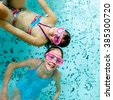 Cute happy young girls children playing in swimming pool  - wearing pink goggles masks - stock photo
