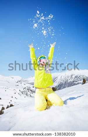 Cute happy young woman in green ski outfit throwing snow in the air - stock photo