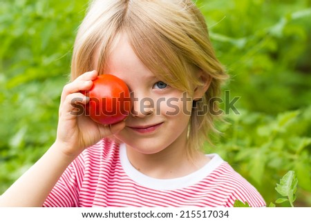 Cute, healthy child in garden holding a tomato over his eye - stock photo