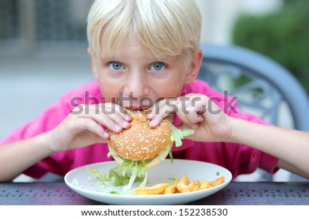 Cute healthy teenager boy eats hamburger with salad and potato sitting in cafe outdoors - stock photo