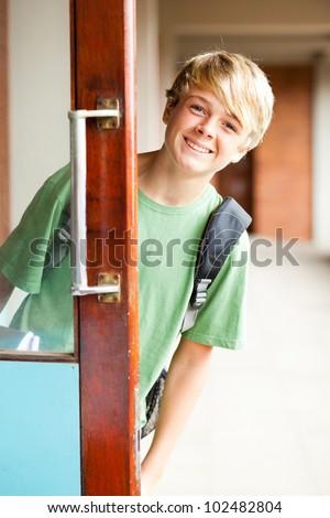 cute high school boy behind classroom door - stock photo