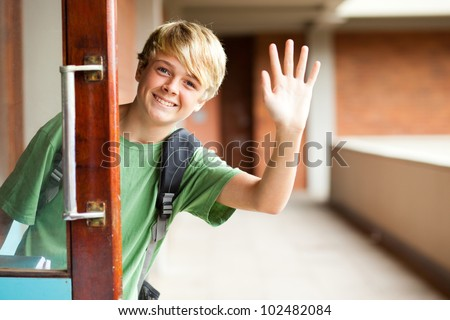 cute high school boy waving good bye - stock photo