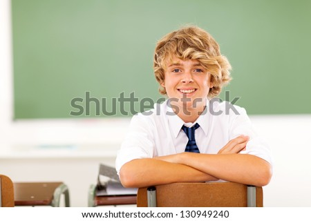 cute high school student sitting in classroom - stock photo