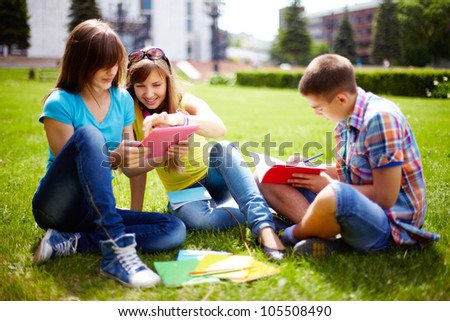 Cute high-school students doing homework outdoor on the lawn - stock photo