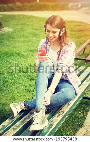 Cute hipster Caucasian teenage girl with smart phone and headphones listening music in park sitting on a bench. Modern young people lifestyle. - stock photo