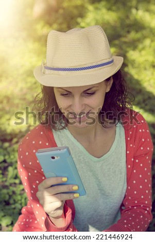 Cute hipster girl text messaging on her smart phone - stock photo