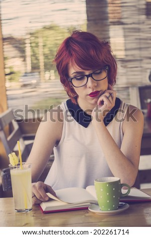 Cute hipster teenage girl reading a book and enjoying coffee  - stock photo