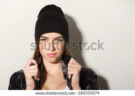 Cute hipster teenage girl with black beanie hat posing looking at camera against white wall. Copy space available.  - stock photo