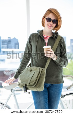 Cute hipster with her bike and disposable cup in front of a window - stock photo